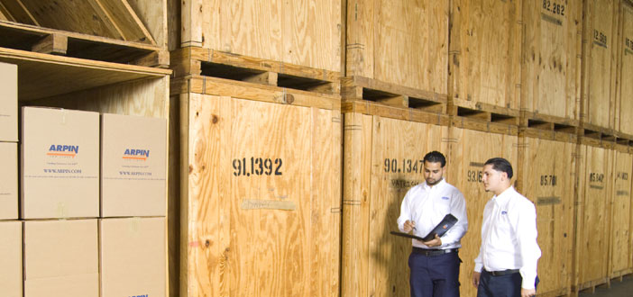 2 Workers standing in front of storage bins in warehouse