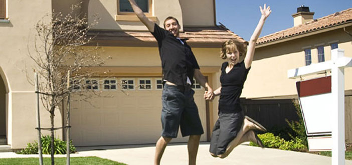 Man and woman holding hands and jumping into the air in front of a house