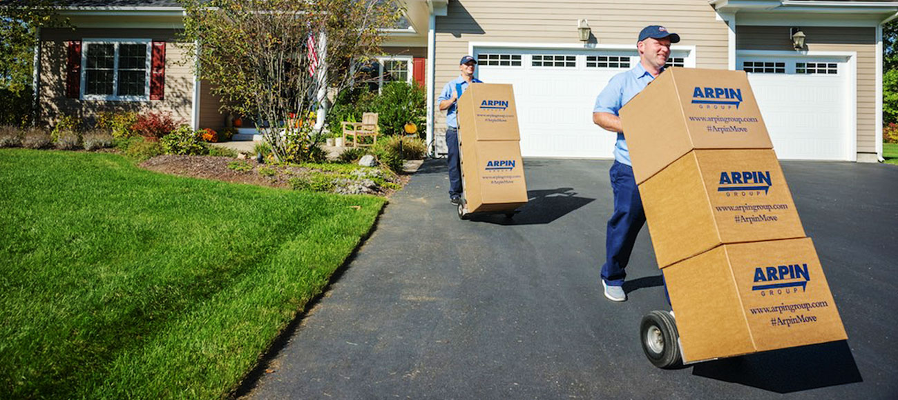2 movers bringing stacks of boxes out of a house